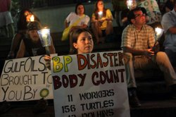 Protesters gather for a candlelight vigil to mark the month anniversary of th...