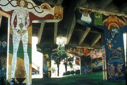 Image of Chicano Park murals painted on concrete pillars which support the Coronado Bridge.