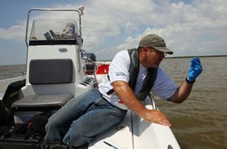 Environmental Protection Agency contractor Andy Kallus collects water samples...
