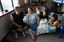 Brian and Julie Morris sit with their three daughters in their room at the Family Gateway homeless shelter in Dallas, Texas.