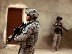 An Iraqi army soldier and a U.S. Army soldier stand guard during a joint patr...