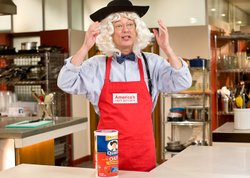 Host Chris Kimball has fun in the test kitchen wearing his Quaker Oats wig an...