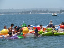 People float on rafts and drink on Sail Bay in Pacific Beach during a Floatop...