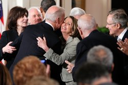 Vice President Joseph Biden hugs Speaker of the House Rep. Nancy Pelosi (D-CA) (C) as widow of the late Sen. Edward Kennedy (D-MA) Vicki Kennedy (L), and Senate Majority Leader Sen. Harry Reid (D-NV) (R) look on after he signed the Affordable Health Care for America Act during a ceremony with fellow Democrats in the East Room of the White House March 23, 2010 in Washington, DC.