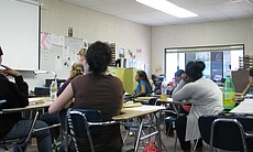 A group of high school students in Vista goes over their classroom assignment.