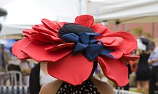 A bright red hat worn by a woman attending opening day at Del Mar Thoroughbre...