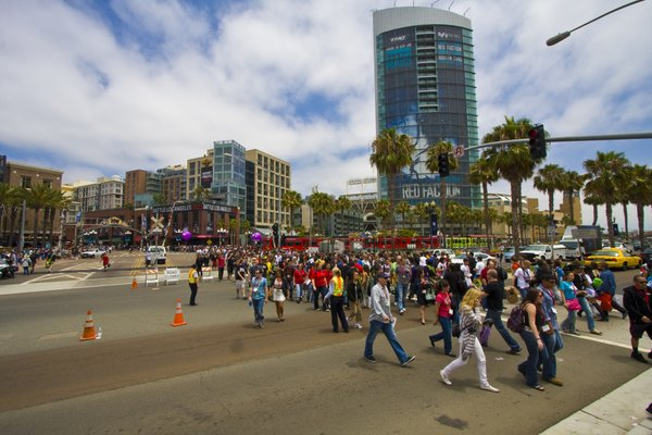 Waves of Comic-Con attendees cross the street headed towards the convention center.