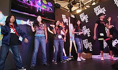 A group of young girls demo the Just Dance 2 video game on the convention floor.