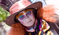 "A young cosplayer at Comic-Con dressed as the Mad Hatter from Tim Burton's ""Alice in Wonderland."""