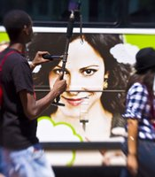 "The face of Mary Louise Parker, star of the Showtime comedy ""Weeds,"" on the side of a bus in front of the convention center."