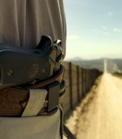 A member of the Minuteman Project watches the fence on the top of his van. He goes nowhere without his loaded Beretta.