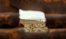 Peering through a hole in the rusty fence, the new barbed wire fence can be s...