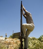 Britt Craig demonstrates how migrants climb the fence using its features as a ladder.