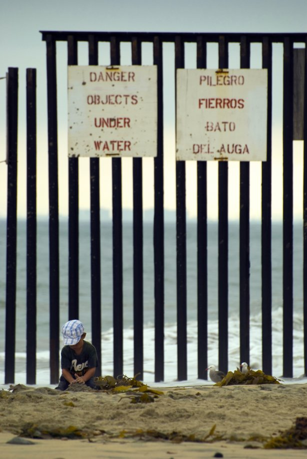 A child plays in the sand while ignoring the fence that stands behind him.