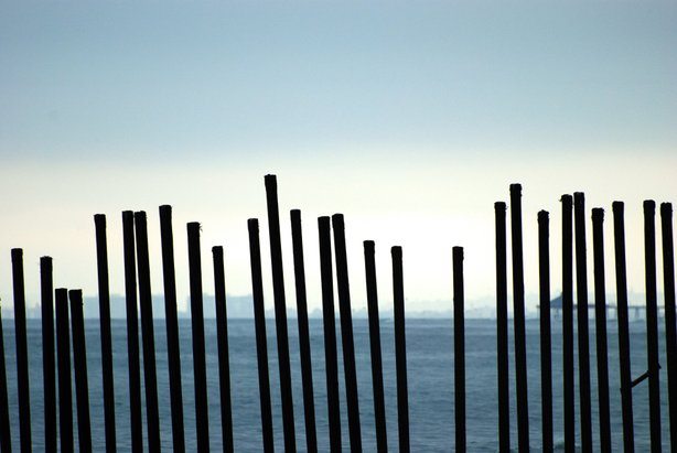 San Diego can be seen on horizon through the border fence at the ocean.