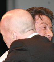 Sylvester Stallone hugs surprise guest Bruce Willis. (Photo by: Tony Weidinger)