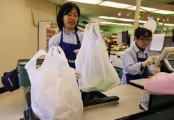 A cashier bags groceries in plastic bags at Nijiya Market June 2, 2010 in San...