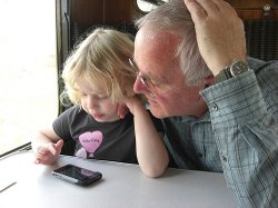 "Natalie Roberts (age 5) reads ""The Little Red Hen"" on the iPhone with her grandfather, Russ."