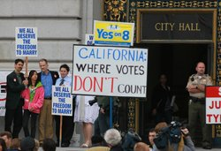 Supporters and opponents of same-sex marriage hold signs as they wait for a d...