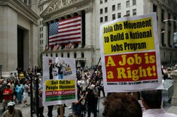 Unemployed workers and other activists protest on the steps of Federal Hall across from the New York Stock Exchange (background) August 12, 2010 in New York, New York.