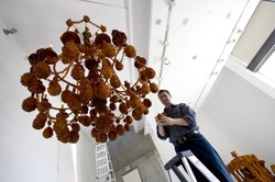 """Lux artist-in-residence Timothy Horn hanging sugar covered baubles on his newly installed baroque chandelier titled """"Diadem."""""""
