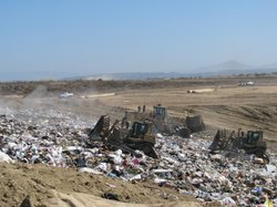 Bulldozers push around piles of trash at San Diego's Miramar Landfill.