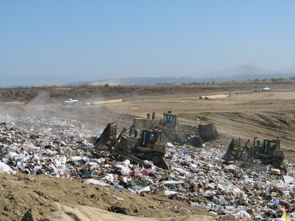 Bulldozers push around piles of trash at San Diego's Mira...