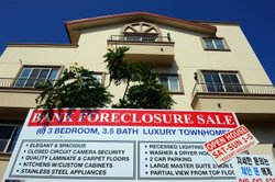 A 'bank foreclosure sale' sign is posted in front of townhomes on August 12, ...