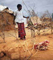 A Somali child stands outside his make-shift home in at a refugee camp in Dadaab, Kenya.