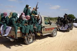 Armed fighters from the al-Shabab terrorist group travel on the back of picku...