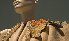 Appliqued button flower motifs adorn one shoulder of the coat designed by Zandra Rhodes on view at the Mingei.