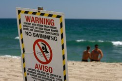 Signs warn the public to stay out of the water in an area harboring high bacteria levels near a drain at Will Rogers State Beach on August 7, 2007 in Pacific Palisades, northwest of Los Angeles, California.