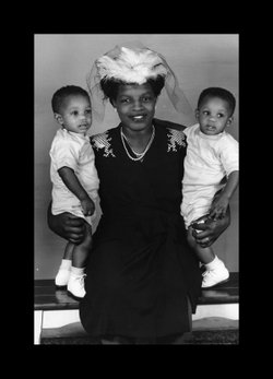 A woman holding twins. Photographed by Norman Baynard.