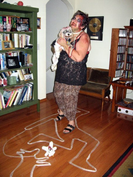 Maggie Mahoney and her dog Moxie turned zombies. The detail of the tape outline on the floor is a touch of genius.