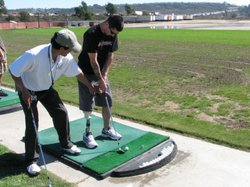 """Jason Lee receives instruction from PGA professional """"AB"""" Nevarez during Operation Game On -- a ten-week program that teaches injured servicemen and women how to play golf, in San Diego, Calif. on October 27, 2010."""