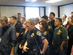 San Diego police officers listen as Chief Lansdowne speaks during a press con...