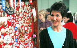 The proud owner stands next to her extensive collection of campaign buttons, ...