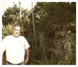 Victor Gonzalez, the owner of Atkins Nursery, stands in front of his oldest chirimoya trees.