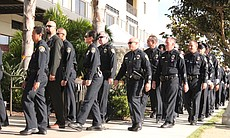 Police officers walk in procession on Rosecrans St. in Point Loma toward the ...