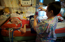 Olivia Welter breathes with the help of the portable ventilator on the back o...