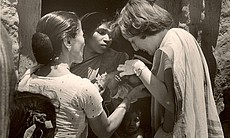 """San Diego resident Mary Jo Clark (right) was a volunteer with the Peace Corps in India from 1967 to 1969.  She is pictured here putting drops into the eyes of a newborn. Clark said, """"This photo was used for an article written about our experiences for the Times of India in 1968.""""  Clark is now a professor of nursing at the University of San Diego."""