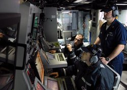 Class Mark Osborne supervises Sonar Technician (Surface) 2nd Class Randy Loewen, right, and Sonar Technician (Surface) 3rd Class Roland Stout, left, as they monitor contacts on an AN/SQQ-89V15 Surface Anti Submarine Combat System at sea.