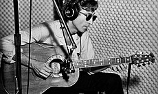 John Lennon playing the guitar with headphones on