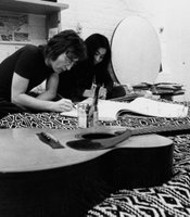 John Lennon and Yoko Ono sitting on a bed writing in New York during the 70s.