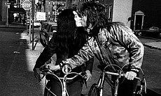 John Lennon and Yoko Ono share a kiss on their bikes in New York during the 7...
