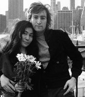 John Lennon standing with his arm around Yoko Ono, who is holding a bouquet of flowers, in New York during the 70s.