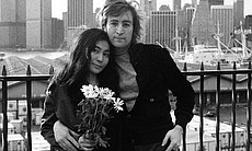 John Lennon standing with his arm around Yoko Ono, who is holding a bouquet o...