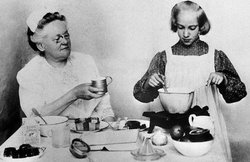 Fannie Merritt Farmer (1857-1915, left) simplified the whole cooking procedure by setting down a system of level measurements that made each recipe turn out exactly right. Here, in a rare photo, Miss Farmer is shown with one of her pupils, Martha Hayes Ludden, at Miss Farmer's Boston cooking school, where recipes were kitchen tested and formulated. Her recipes have become so popular that her cookbooks sold in the millions, while a large candy company utilizing some of her candy recipes currently sells some 20 million pounds of candies yearly. Undated.