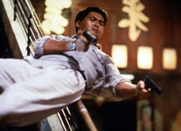 Chow Yun Fat sliding down the banister with two guns blazing in John Woo's Hard-Boiled.""