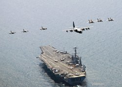 A U.S. Marine Corps C-130 Hercules aircraft leads a formation of F/A-18C Hornet strike fighters and A/V-8B Harrier jets over the aircraft carrier USS George Washington July 27, 2010 off the coast of South Korea.